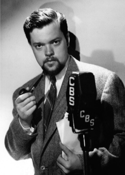 "A very young looking Orson Welles, complete with beard for a concurrent Mercury stage production, poses for a CBS photo publicizing the upcoming premier of ""The Mercury Theatre on the Air""."